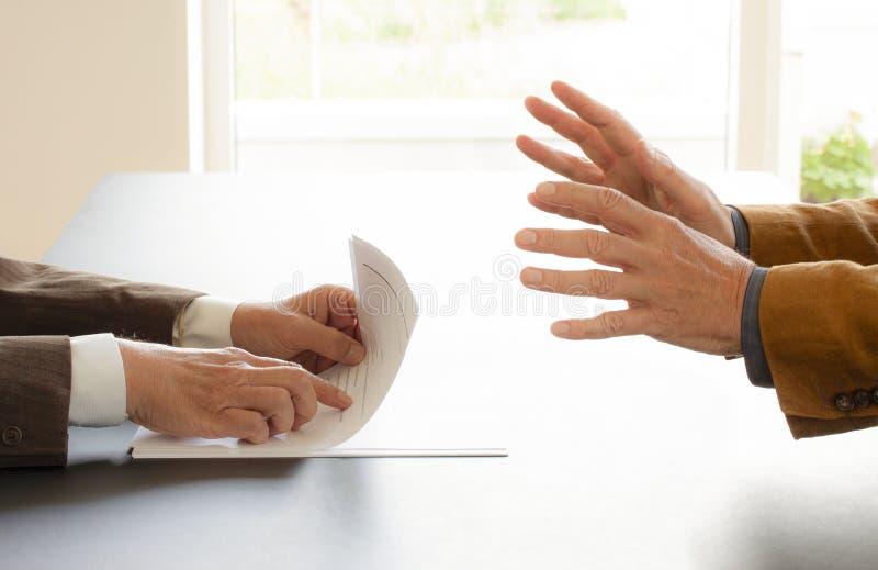 Handen van twee zakenlieden in gesprek door een bureau Het onderhandelen zaken of een baangesprek - Beeld stock foto's