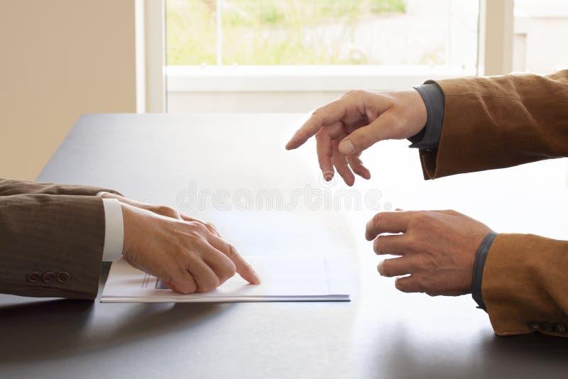 Handen van twee zakenlieden in gesprek door een bureau Twee koppen van koffie op de lijst Het onderhandelen zaken of een baangesp stock foto