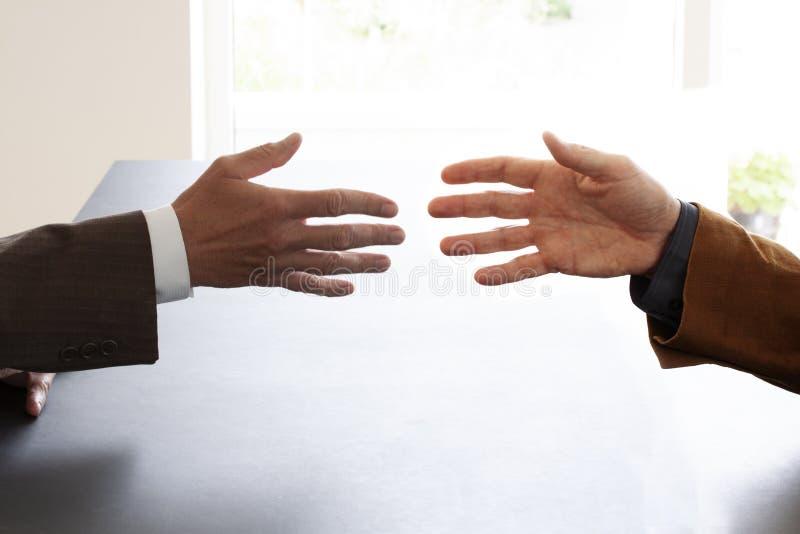 Handen van twee zakenlieden in gesprek door een bureau ongeveer om handen te schudden Het onderhandelen zaken of een baangesprek  royalty-vrije stock foto's
