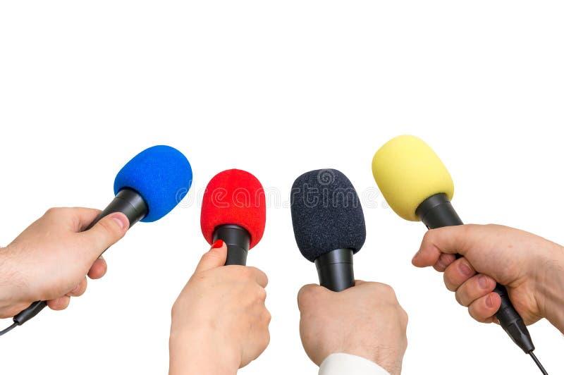 Handen van verslaggevers met vele microfoons stock afbeelding