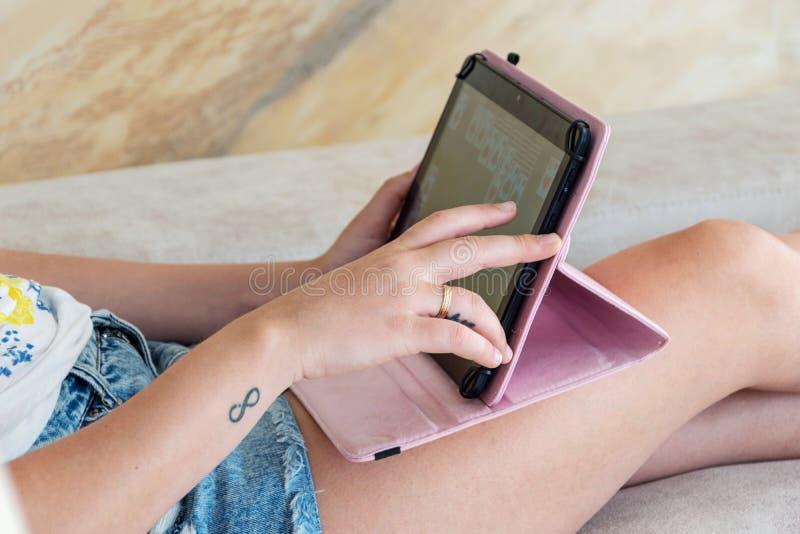 Handen van vrouw die een tablet thuis gebruiken royalty-vrije stock afbeeldingen