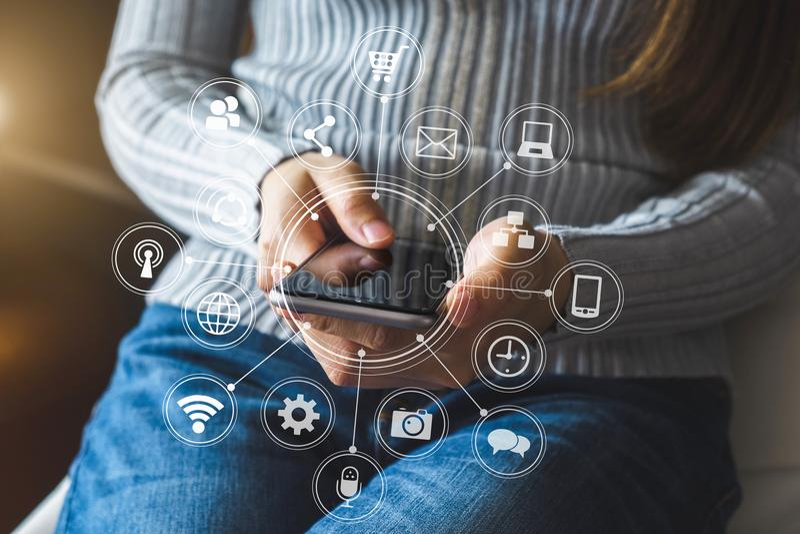 Handen van vrouw die mobiele telefoon in modern bureau met laptop en digitale tabletcomputer met behulp van stock foto