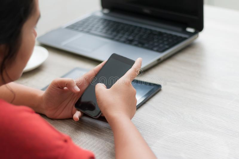 Handen van vrouw die smartphone op houten lijst gebruiken stock afbeelding