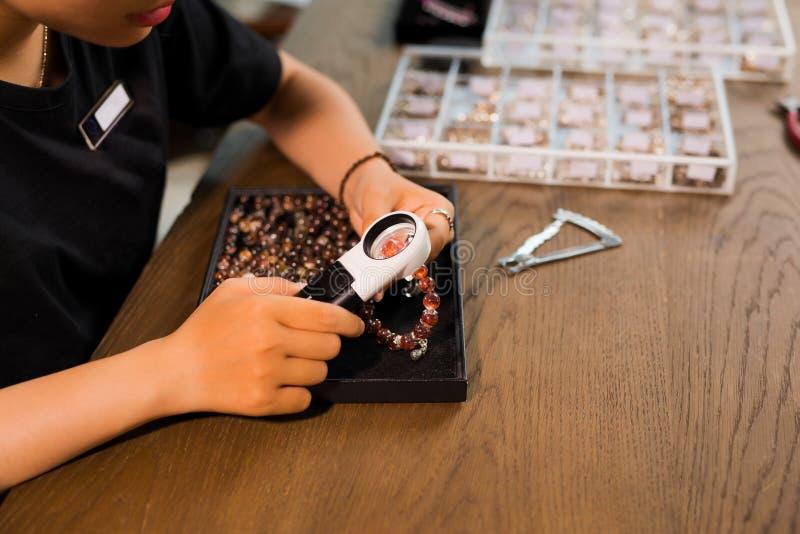 Handen van vrouwelijke juwelenontwerper die haar werk met magnif bekijken stock afbeeldingen