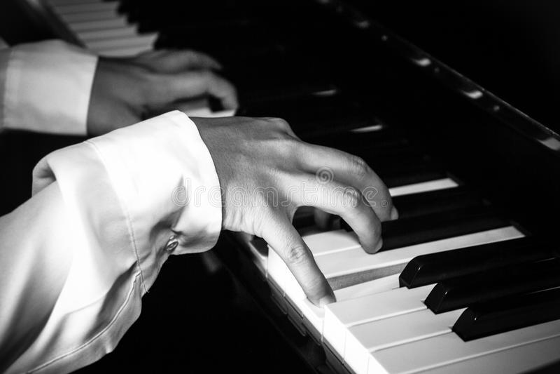 Handen van vrouwelijke pianist/musicus het spelen piano stock fotografie