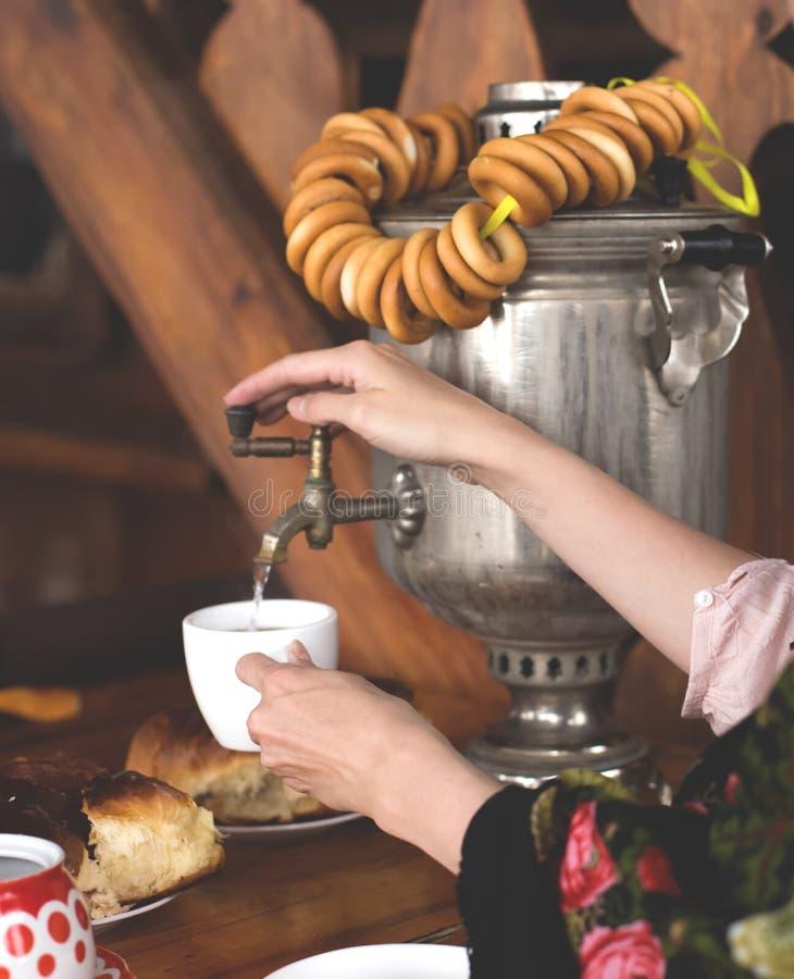 Handen van vrouwen openden de kraan van de samovar en namen warm water in een mok thee stock foto