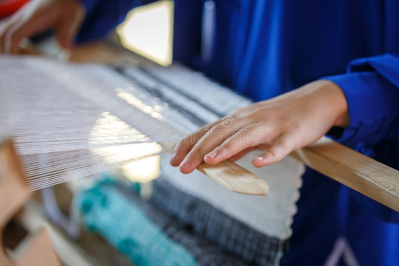 Handen van vrouwen wevende stof op een houten weefgetouw r stock foto