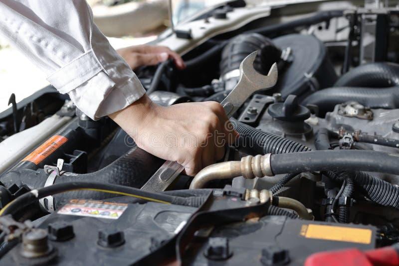 Handen van werktuigkundige met moersleutel die motor van auto herstellen onder autokap royalty-vrije stock fotografie