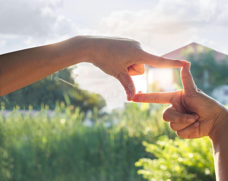 Handensymbool voor huis op de achtergrond van de zonneschijnaard stock foto's