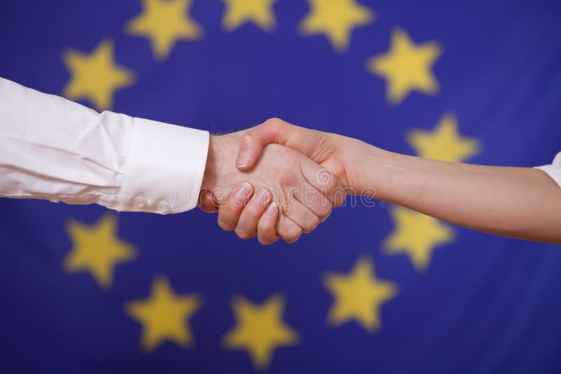 Handerschütterung über europäischer Markierungsfahne stockbild