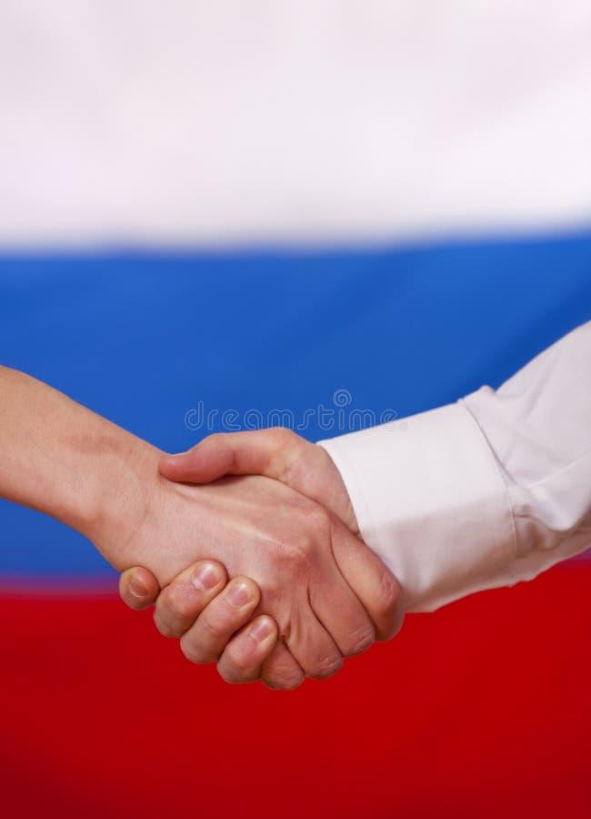 Handerschütterung über russischer Markierungsfahne stockfotografie