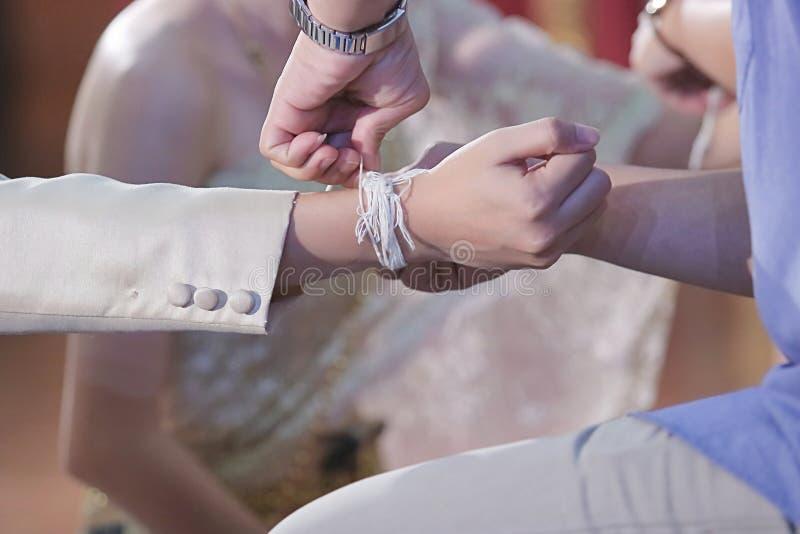 Handfasting Fuoco selettivo sulle mani di cerimonia di nozze tailandese immagini stock