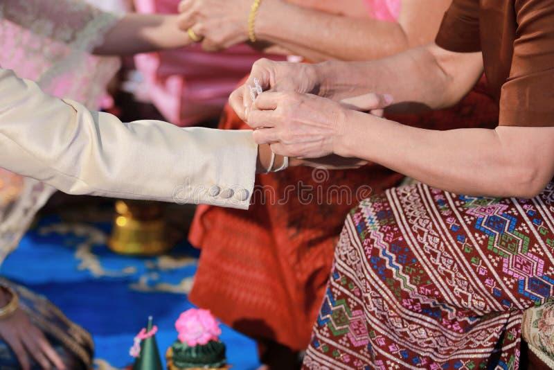 Handfasting. Selective focus on hands of Thai wedding ceremony. stock photo