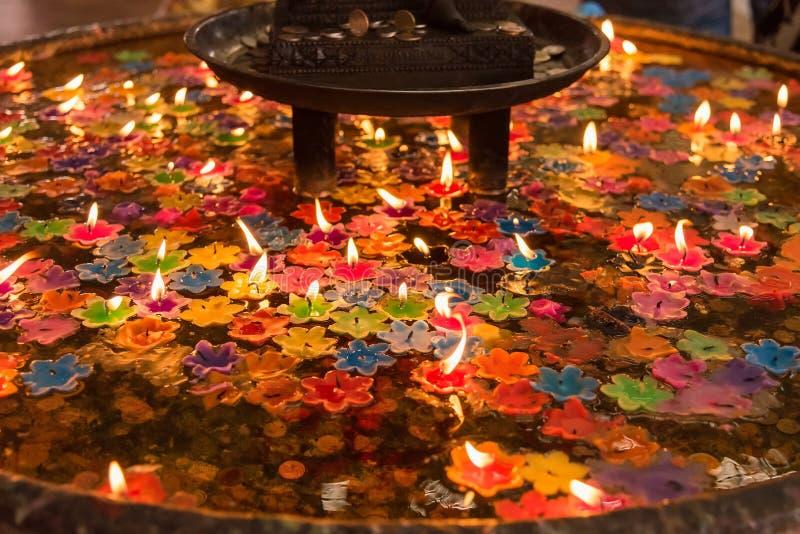Handfat för heligt vatten för att sväva blommastearinljuset för att be till guden för arkivbild