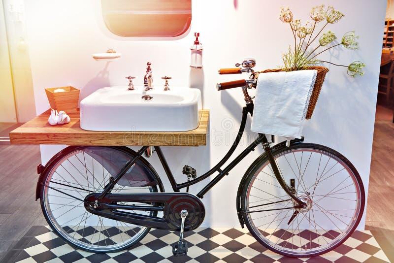 Handfat och retro cykel i badrum arkivbild