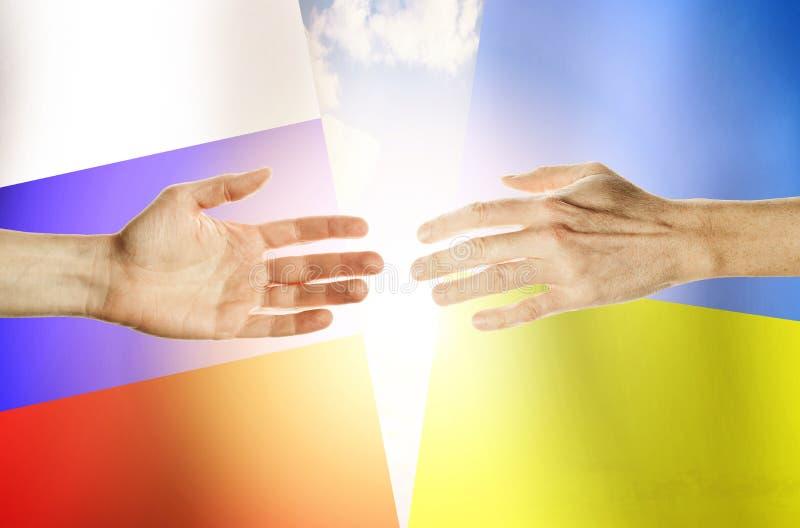 Handfolk mot bakgrundflaggorna Ryssland och Ukraina royaltyfria bilder