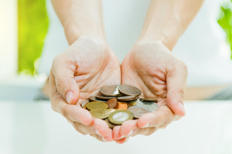 Handful of coins in palm hands,Businessman holding plant sprouting from a handful of coins,finance concept,business background stock images