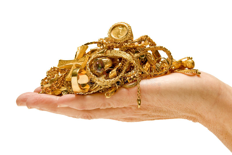 Hand holding gold jewelry. Hand holding pile of gold jewelry on white background stock photography
