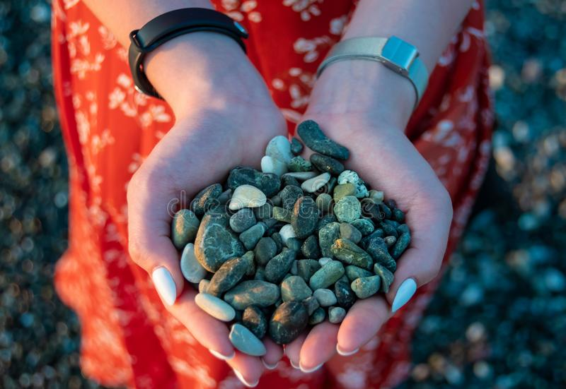 Handful of green pebbles in hands. Perfect clean pebble beaches on the coast of Liguria. Handful of green pebbles in hands. Perfect clean pebble beaches on the stock photos