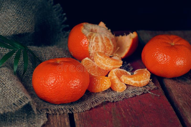 A handful of mandarin lies on a wooden table, some are cleaned and divided into slices stock photography