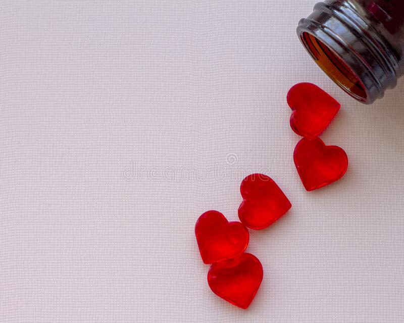 a handful of red pills in the shape of hearts near the jar. royalty free stock photo