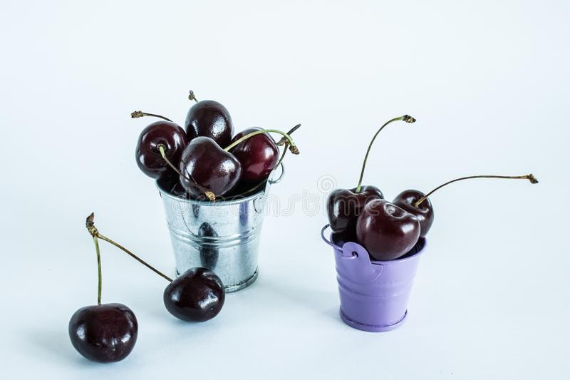 A handful of ripe cherries in small buckets close-up. A handful of ripe large cherries in small metal decorative buckets close-up royalty free stock photography