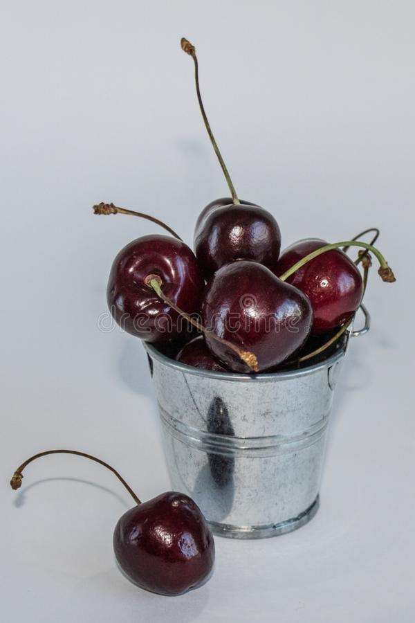 A handful of ripe cherries in small buckets close-up. A handful of ripe large cherries in small metal decorative buckets close-up stock photo