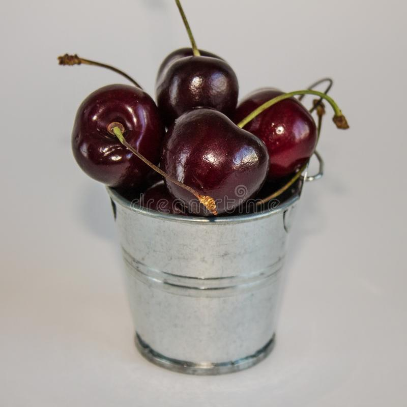 A handful of ripe cherries in small buckets close-up. A handful of ripe large cherries in small metal decorative buckets close-up royalty free stock images