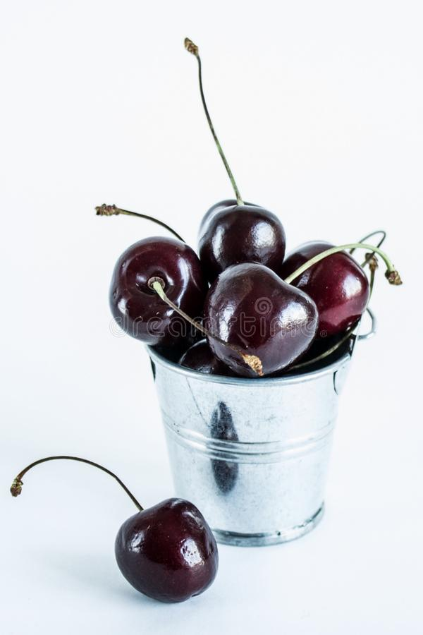 A handful of ripe cherries in small buckets close-up. A handful of ripe large cherries in small metal decorative buckets close-up stock images