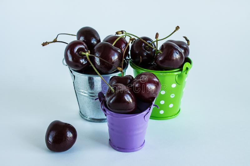 A handful of ripe cherries in small buckets close-up. A handful of ripe large cherries in small metal decorative buckets close-up stock image