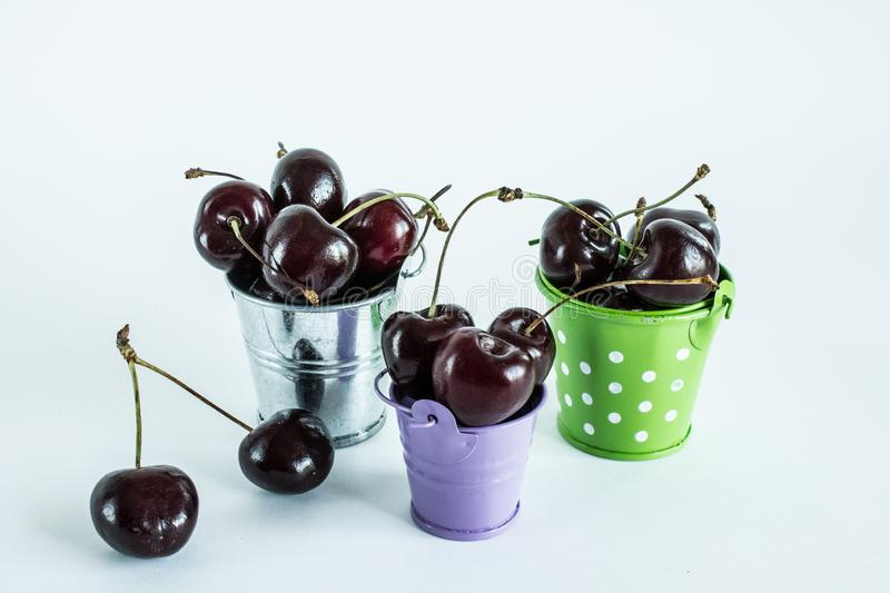 A handful of ripe cherries in small buckets close-up. A handful of ripe large cherries in small metal decorative buckets close-up stock photography