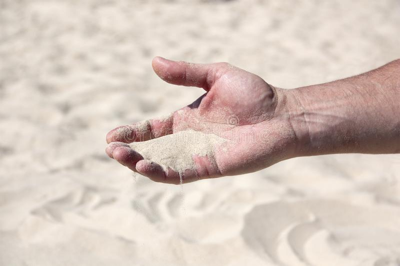 A handful of sand in the human palm. Close-up stock image