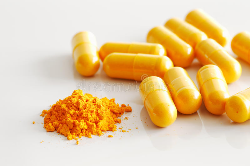 A handful of turmeric capsules with the contents of one spilled stock photography