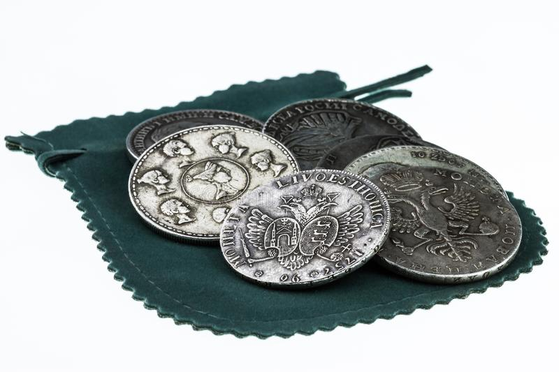 Handful of vintage coins and wallet. A handful of vintage coins and a wallet on a white background close-up stock photo