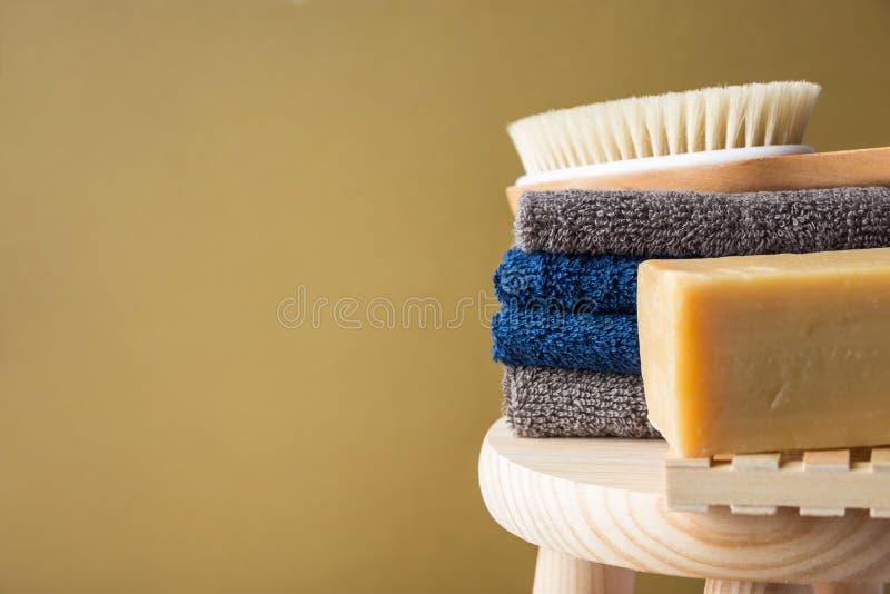 Handgefertigte Olivenölseifenkörperbürste des Handwerkers faltete die Baumwolltücher, die auf Holzstuhl gemaltem beige Wandhinter stockbild