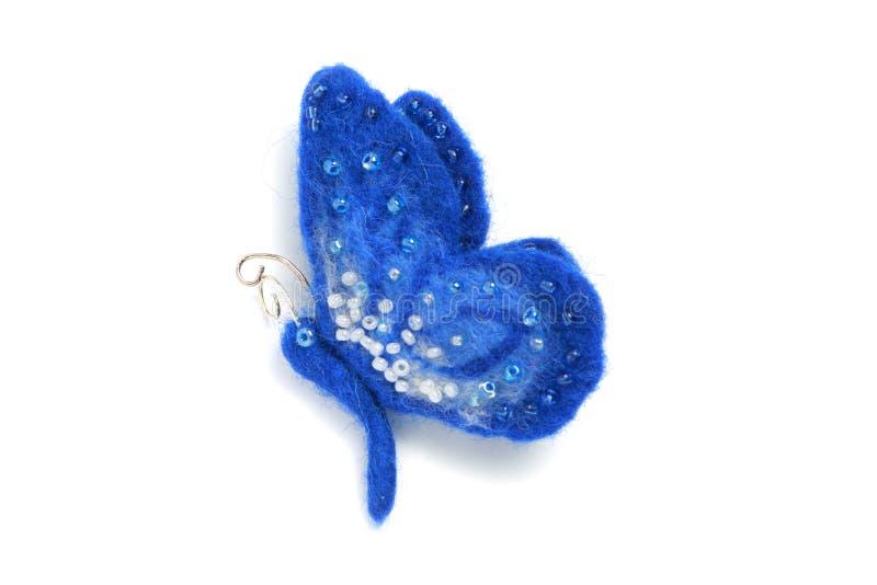 Handgemachte Brosche vom Filz in Form eines blauen Schmetterlinges, verziert mit Perlen auf einem weißen Hintergrund stockfotos