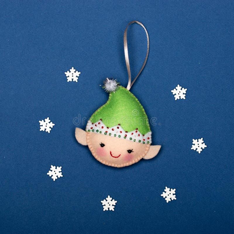 Handgemachte Elfe des Filzes liegend auf einem blauen Hintergrund mit Schneeflocken stockfoto