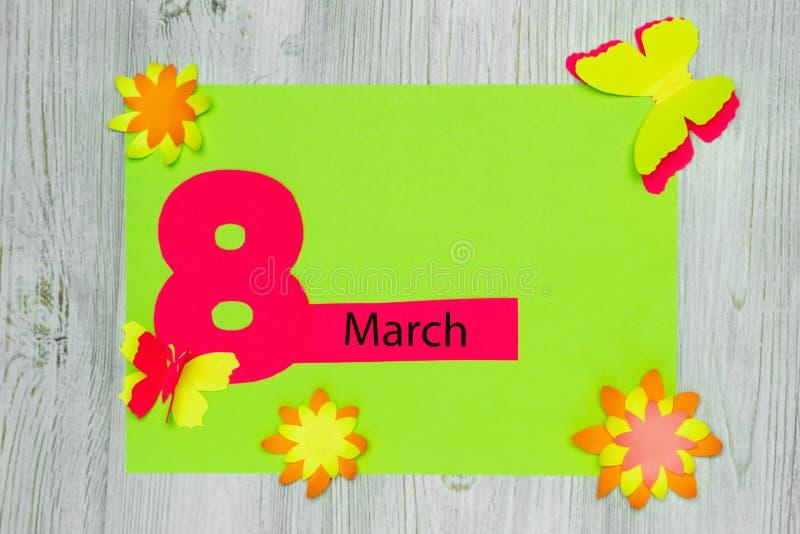 Handgemachte Grußkarte Die Aufschrift am 8. März und die Blumen und die Schmetterlinge des Papiers Flache Lage Kopieren Sie Platz lizenzfreies stockfoto