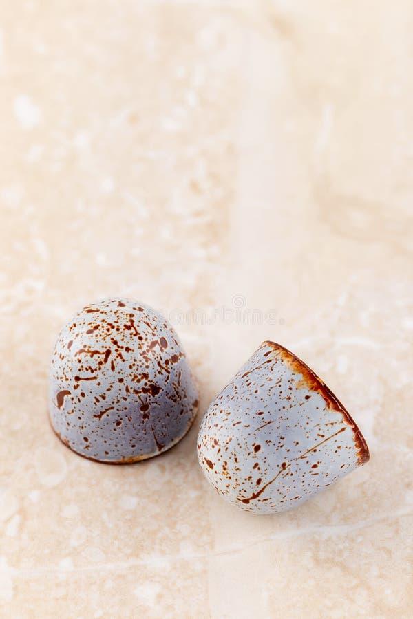 Handgemachte LuxusPraline verziert mit Farbenstellen auf beige Marmorhintergrund lizenzfreies stockfoto