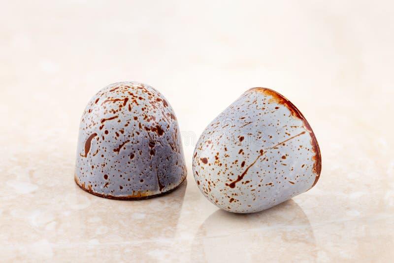 Handgemachte LuxusPraline verziert mit Farbenstellen auf beige Marmorhintergrund lizenzfreies stockbild