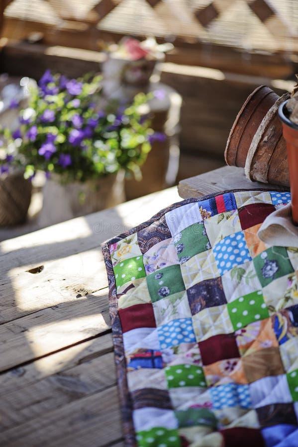 Handgemachte Patchworkdecke auf Holztisch mit Frühling blüht auf Hintergrund lizenzfreie stockfotografie