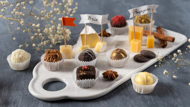 Handgemachte Schokoladenkäsesorten, weiße, dunkle und Milchschokolade und verschiedene Käsearten auf dem Teller Feinschmecker-Des stockbilder