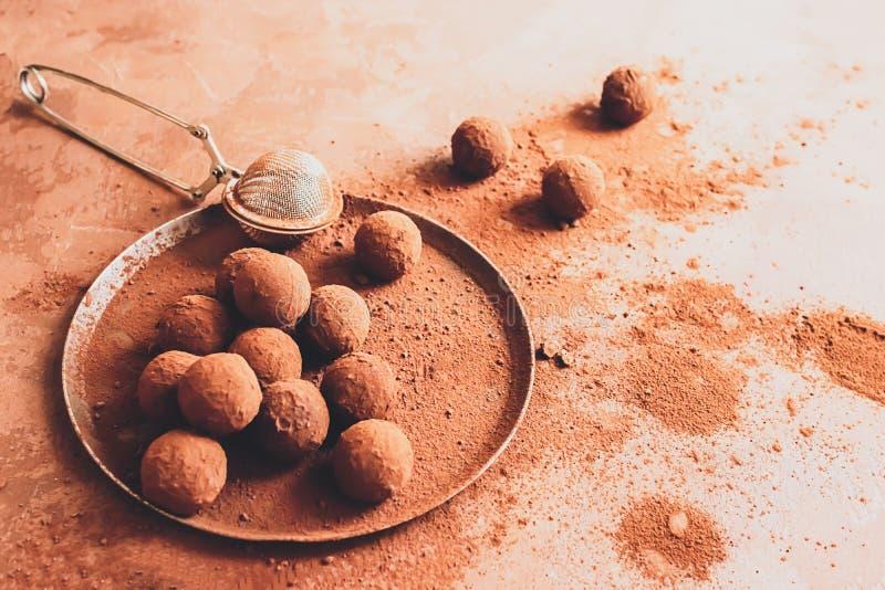 Handgemachte Schokoladentrüffel auf einer Platte Dunkle Pralinen im Kakaopulver auf einem dunkelbraunen Hintergrund Flacher Plan lizenzfreies stockbild