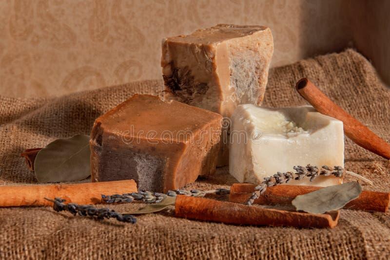 Handgemachte Seife auf der Serviette mit Zimt, Lorbeer, Kamille, Anis, Sternanis, Rosmarin, Thymian, Hafermehl, lavanta stockfotos