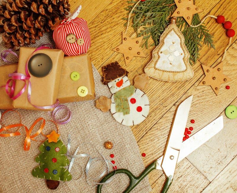 Handgemachte Weihnachtsgeschenke in der Verwirrung mit Spielwaren, Kerzen, Tanne, Band, hölzerne Weinlese des Baumkegels, Postkar stockfoto