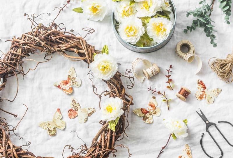 Handgemachter Hauptinnenausstattungsweinstockkranz mit Papierblumen und Schmetterlingen auf einem hellen Hintergrund, Draufsicht  stockfotografie