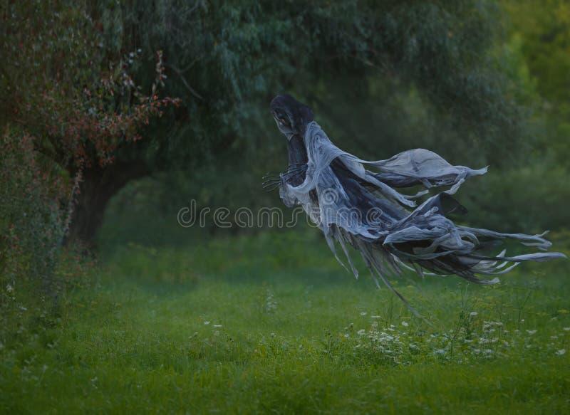 Handgemachter Tod fliegt durch die Luft mit einem gewellten Umhang in den Wald über dem Rasen mit grünem Gras Autumn Summer stockfotografie