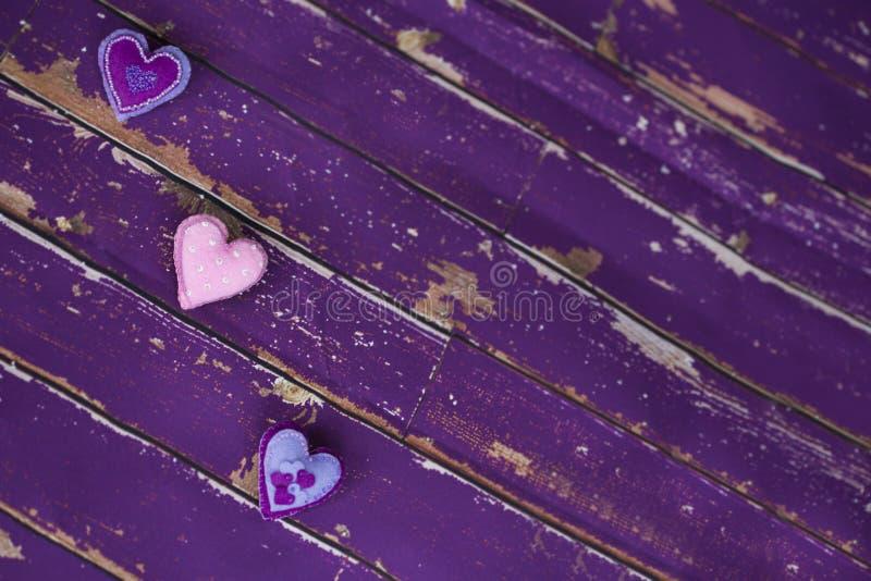 Handgemachtes Gewebe glaubte Spielzeugherzen auf altem violettem Bretterboden lizenzfreies stockbild