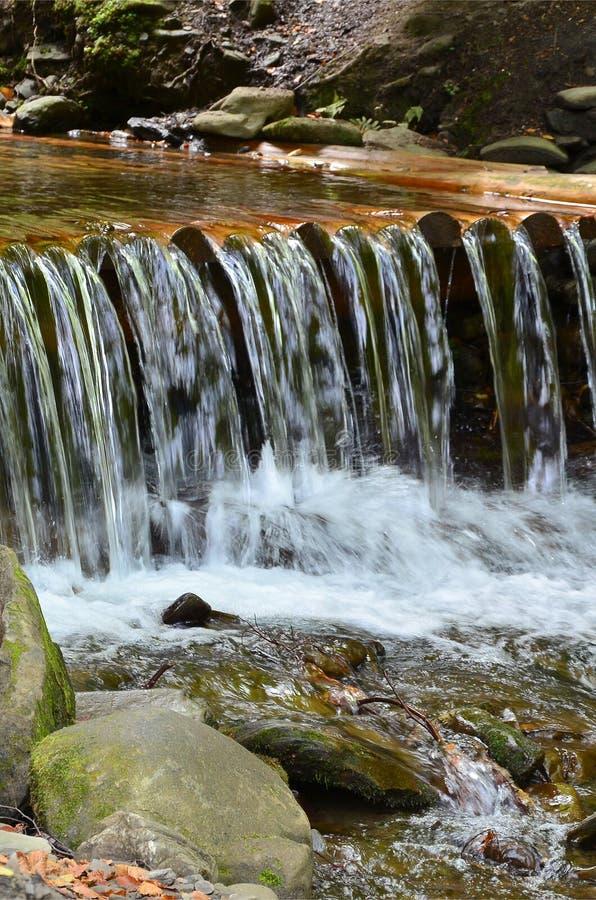 Handgemachtes hölzernes Wasser fließt kleine behandelte Strahlen Ein schönes Fragment eines kleinen Wasserfalls lizenzfreie stockfotografie