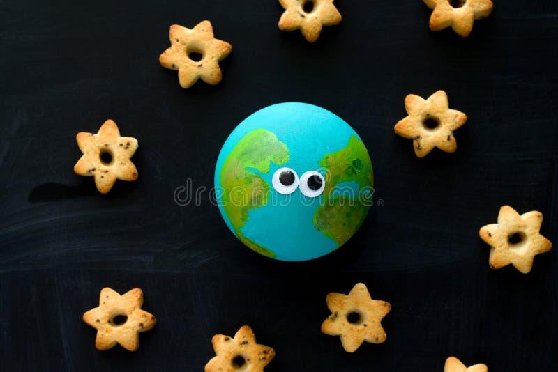 Handgemachtes Modell der Draufsicht des Erdplaneten mit lustigen googly Augen und Plätzchen in Form der Sterne auf der Tafel, Rau stockbilder